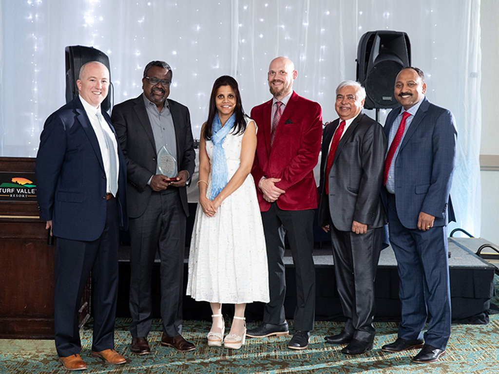C-HIT leadership team poses with a recipient of a performance award at the 2019 Corporate Holiday party.