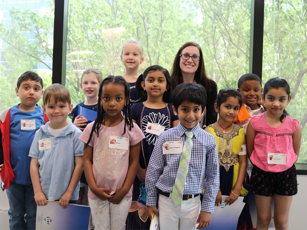 Children pose with their Group Leader at the 2019 Take Your Child to Work day in C-HIT's corporate offices.